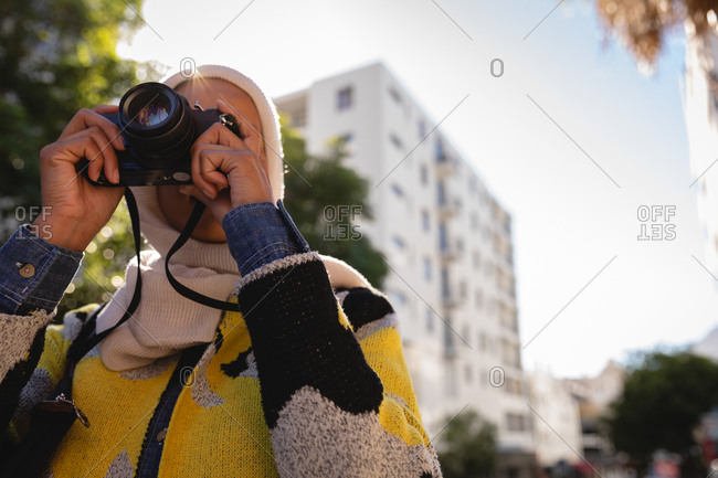 Low angle view of a mixed-race woman taking a picture with her digital camera at street on a sunny day