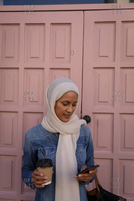 Front view of a beautiful mixed-race woman using mobile phone and holding a coffee while standing in front of door in the street