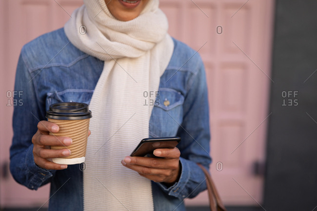 Mid section of woman using mobile phone and holding coffee while standing in front of door in the street