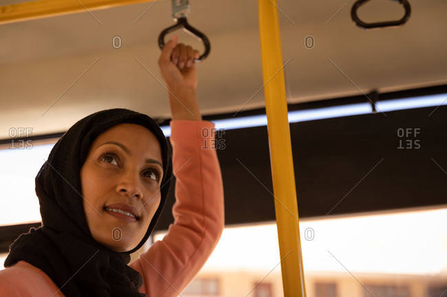 Low angle view of a beautiful mixed-race woman standing in the bus