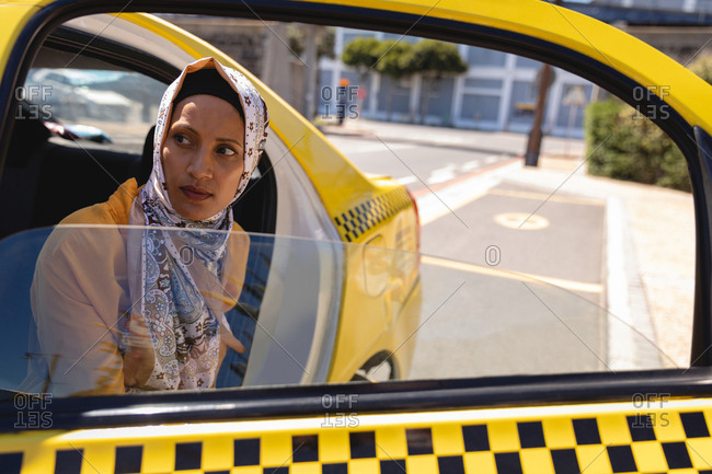 Front view of stressed mixed race woman coming out of taxi on a sunny day