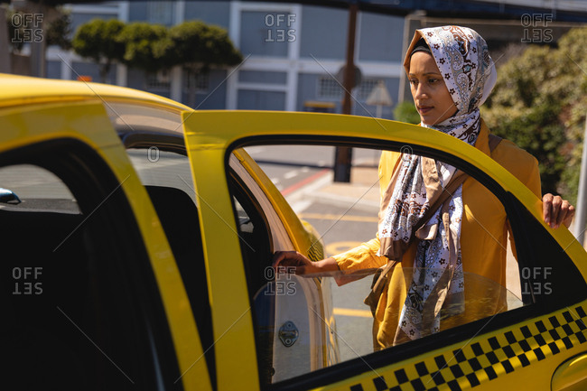 Front view of thoughtful mixed race woman getting in the taxi in the street