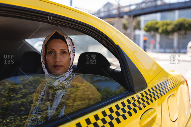 Front view of thoughtful mixed race woman looking at the camera while sitting in taxi on a sunny day