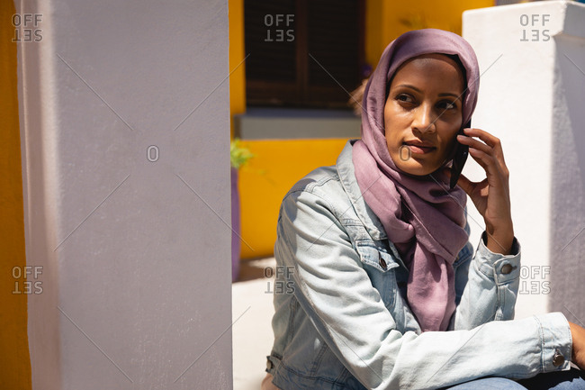 Front view of thoughtful beautiful mixed race woman with hijab sitting in front of her house while talking on mobile phone