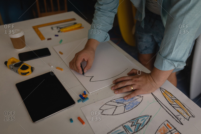 Mid section of Caucasian man drawing surfboard sketch in a workshop. Tablet, coffee, ruler, pencils, crayons, paper, and mobile phone are displayed on the table.