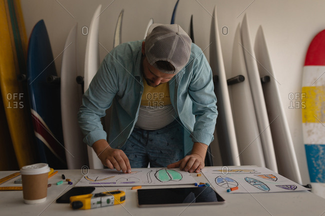 Front view of Caucasian man drawing surfboard sketch in a workshop