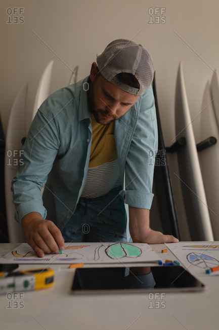 Front view of concentrated Caucasian man making surfboard sketch in a workshop