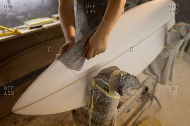 Mid section of Caucasian man cleaning surfboard with a cloth in a workshop