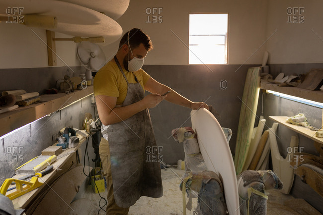 Side view of Caucasian man with mouth protection mask using mobile phone while cleaning surfboard in a workshop