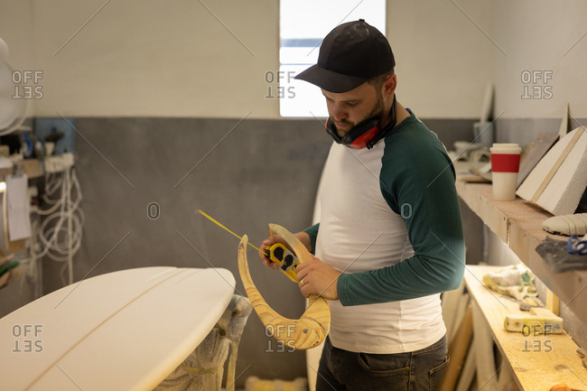 Side view of Caucasian man measuring surfboard with special ruler in a workshop