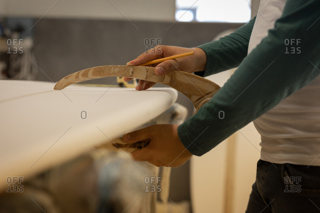 Mid section of Caucasian man measuring surfboards thickness with specific material while holding pencil in a workshop.