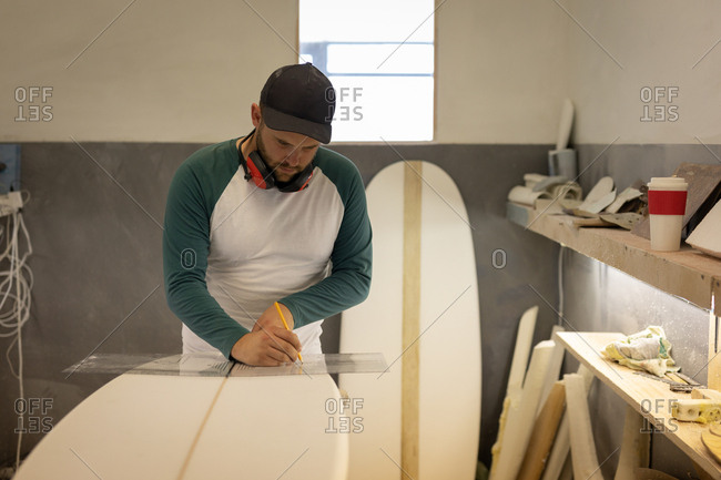Front view of handsome Caucasian man with earmuffs measuring with ruler and pencil a surfboard in workshop
