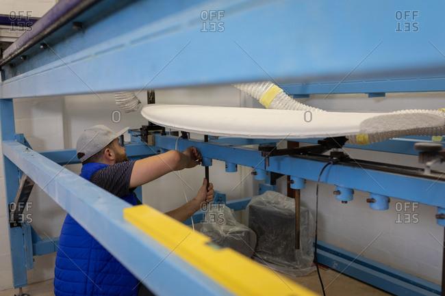 Side view of Caucasian man making a surfboard in workshop