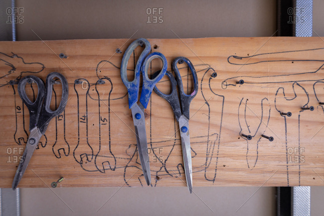 Three scissors hanging on nail at workshop