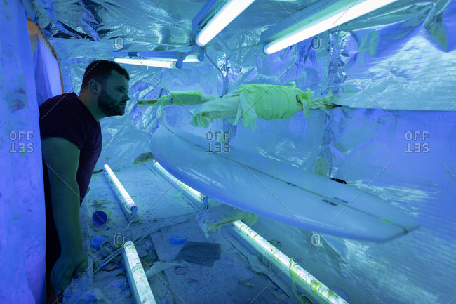 Side view of handsome Caucasian man looking at surfboard in special UV room in workshop