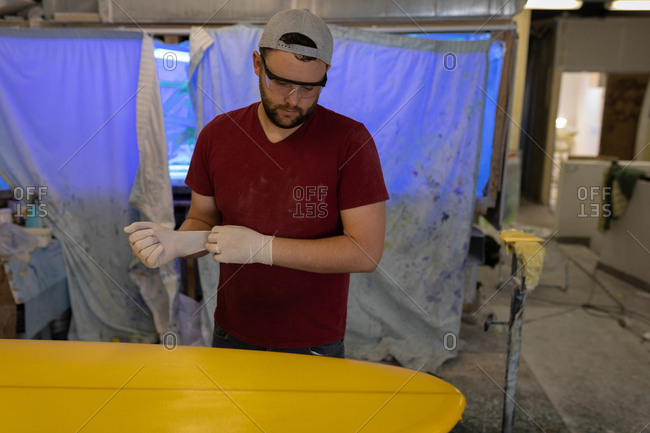 Front view of handsome Caucasian putting latex gloves on while standing in front of surfboard in workshop.