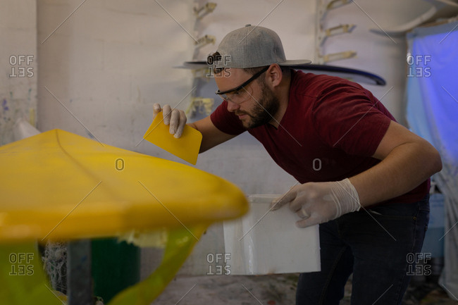 Side view of Caucasian man applying yellow sanded matt on the surfboard in surf shop.