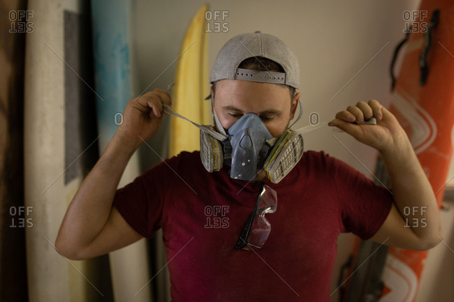 Front view of concentrated Caucasian man wearing gas mask in a surf workshop