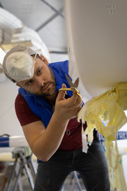Low angle view of concentrated Caucasian man making a surfboard in surf shop. He is cutting protective veil in workshop