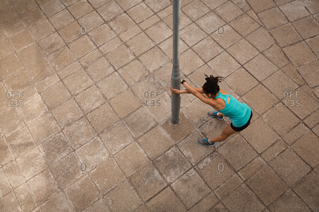 High angle view of young Mixed race woman listening music on earphones while exercising in the city