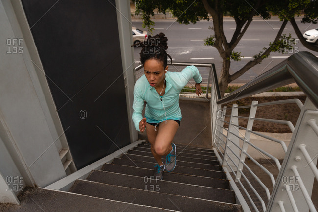 High angle view of young Mixed race woman listening music on earphones while exercising on stairs in the city