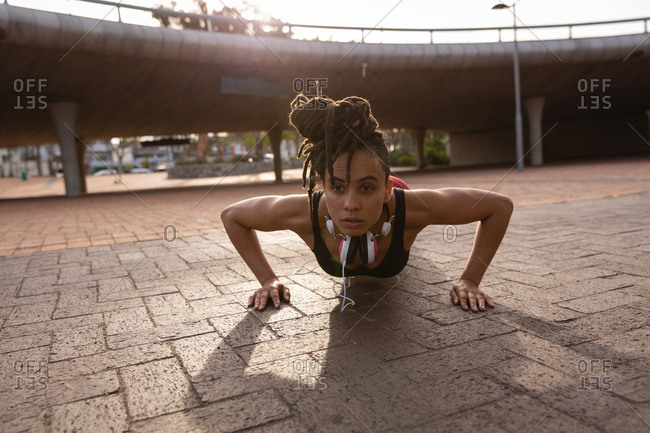 Front view of fit young Mixed race woman doing push-up exercise in the city