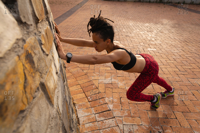 Side view of fit young Mixed race woman exercising in the city