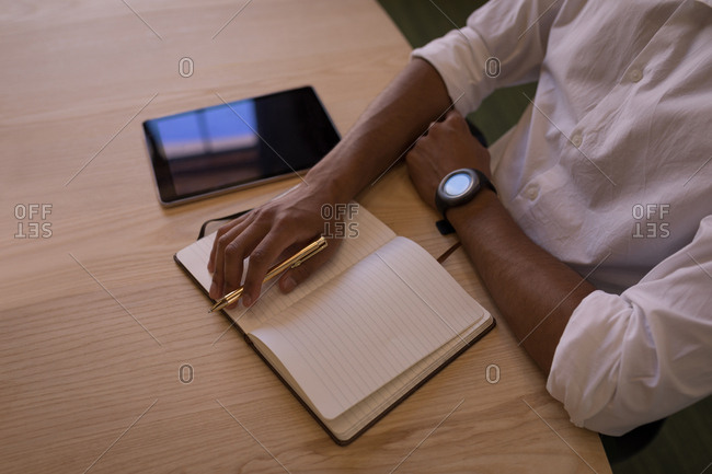 High angle view of thoughtful mixed-race businessman sitting at wooden desk with notebook, a pen and a digital tablet
