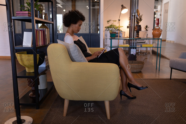 Side view of beautiful mixed-race businesswoman using digital tablet in modern office while she is sitting on a modern seat against furnishings in background