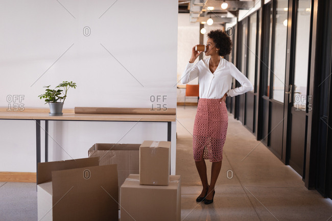 Front view of beautiful Mixed-race businesswoman drinking coffee standing in modern office