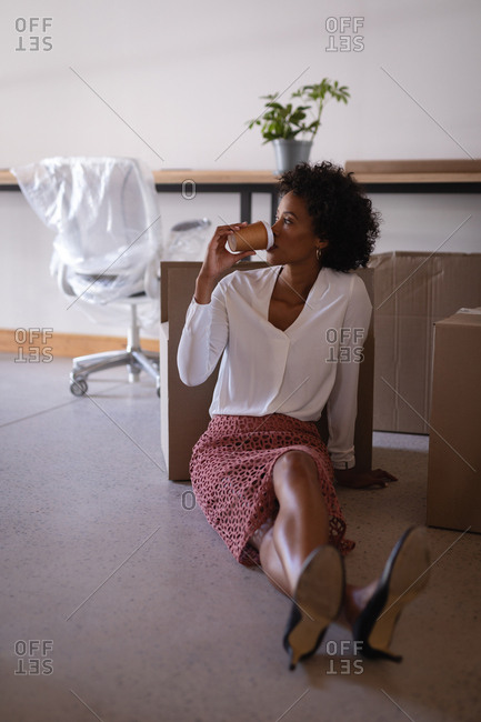 Front view of beautiful mixed-race businesswoman relaxing while drinking coffee sitting on floor in modern office