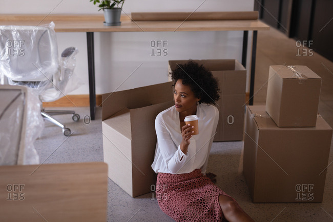 Low angle view of thoughtful mixed-race businesswoman having coffee while sitting on floor against cartons in modern office
