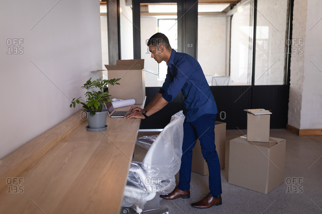 Side view of young mixed-race businessman using laptop at desk in new office