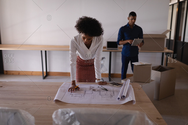 Front view of Mixed-race businesswoman looking at blueprint while mixed-race businessman using digital tablet at office in background