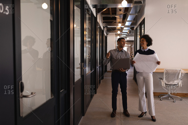 Front view of happy young Mixed-race business people interacting with each other in office while they are holding a blueprint