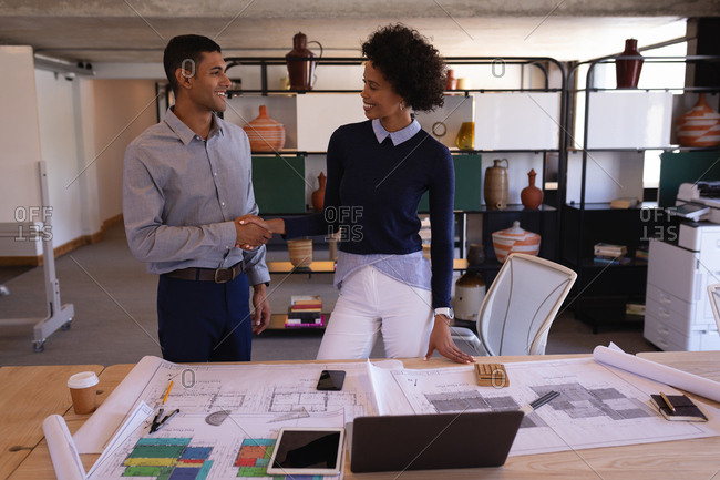 Front view of happy mixed-race business people shaking hands with plans in foreground on desk.