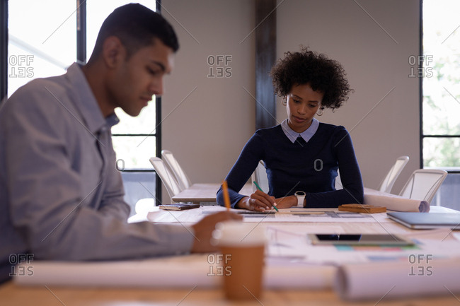 Front view of focused young Mixed-race business people working on plans with pencils in a meeting room