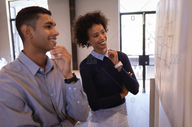 Side view of happy Mixed-race business people looking at plans stick on the wall while. They are touching their chin at office