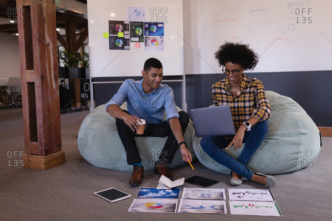 Front view of happy young Mixed-race business people discussing over graph sitting in modern office