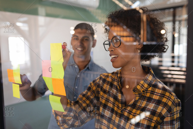 Front view of happy Mixed-race business people writing on sticky notes standing in modern office