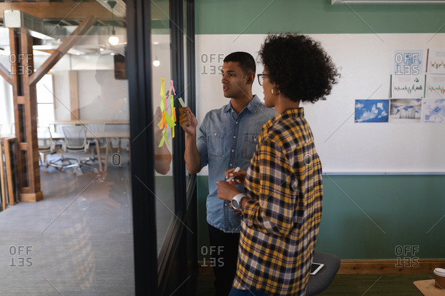 Side view of young Mixed-race business people writing on sticky notes standing in modern office