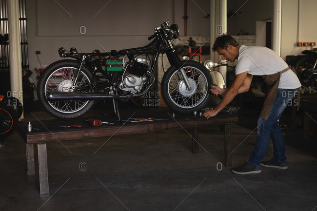Side view of Caucasian bike Mechanic repairing bike in garage