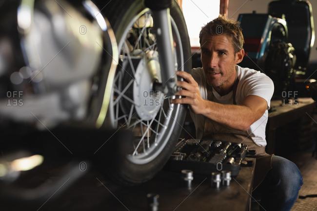 Front view of Caucasian bike Mechanic repairing bike in garage