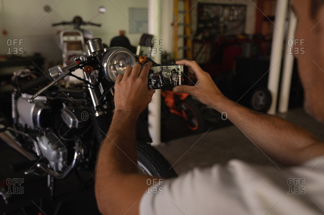 Rear view of matured Caucasian bike mechanic capturing photo of bike in garage