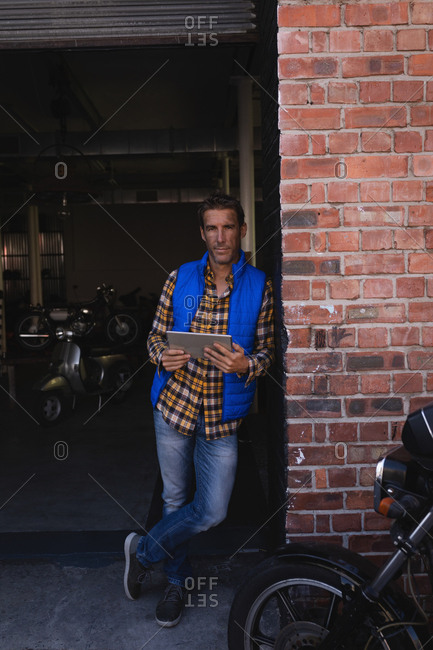 Front view of Caucasian bike mechanic leaning at brick wall while holding digital tablet in garage