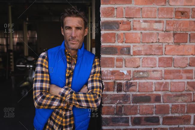 Portrait of Caucasian bike mechanic leaning at brick wall while arms crossed in garage