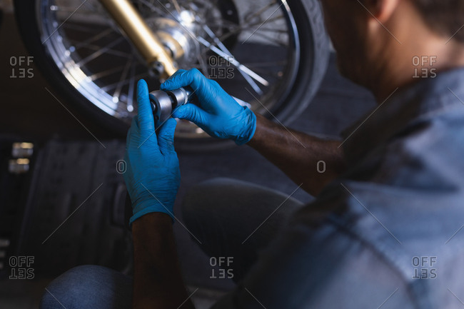 High angle view of Caucasian bike mechanic working in garage with ratchet wrench