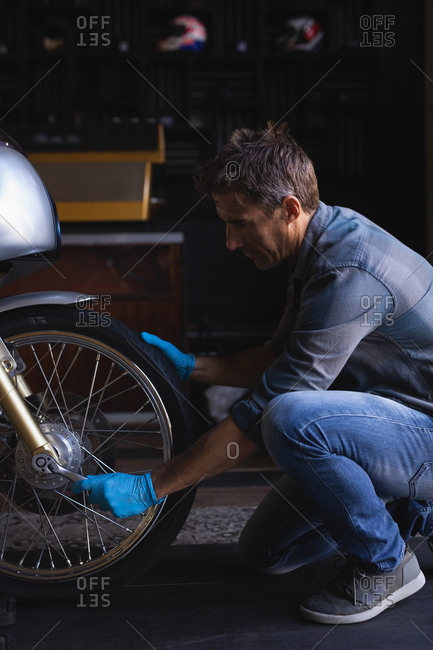 Side view of Caucasian bike mechanic using ratchet wrench to adjust bike tire