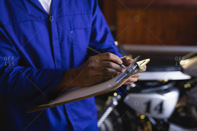 Mid section of caucasian bike mechanic maintaining automobile records on clipboard at garage