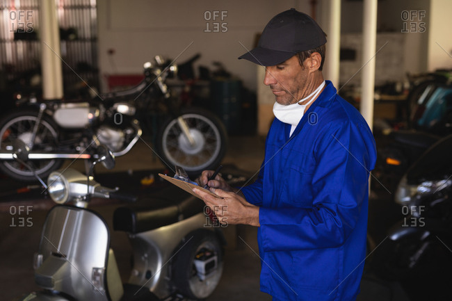 Side view of Caucasian bike mechanic maintaining automobile records on clipboard at garage